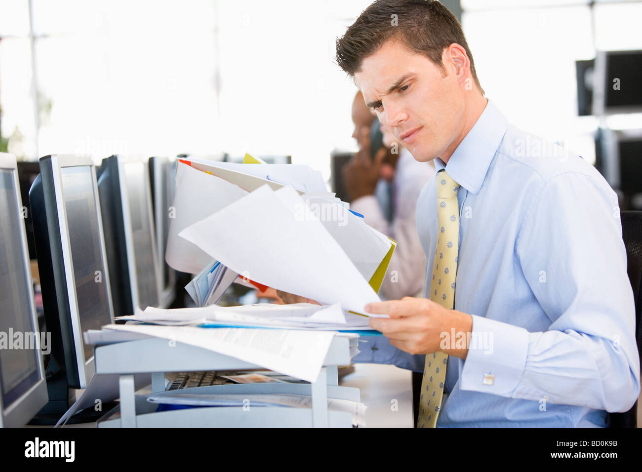 Stock Trader Looking Though Paperwork - Stock Image