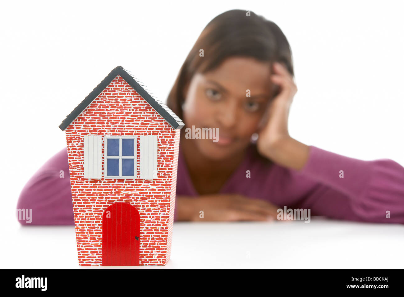 Woman Looking At Model House - Stock Image