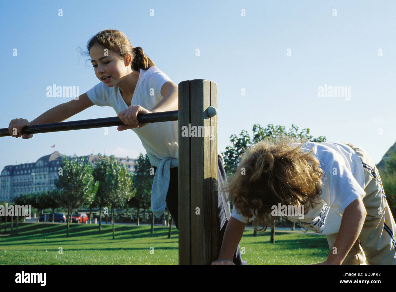 Girls playing on bars at park Stock Photo