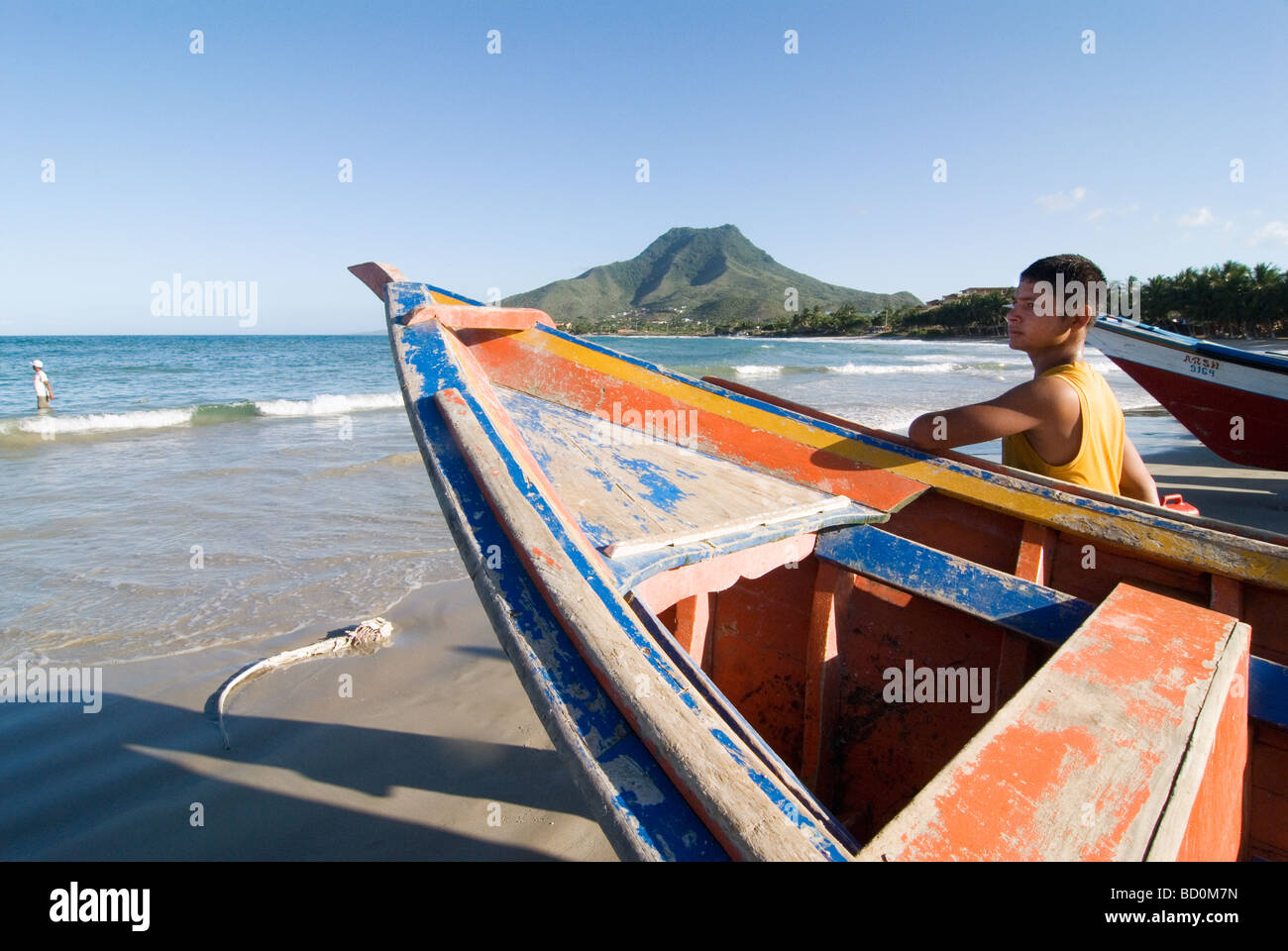 Boy beneath a fisherboat on the island Isla de Margarita, Venezuela. - Stock Image