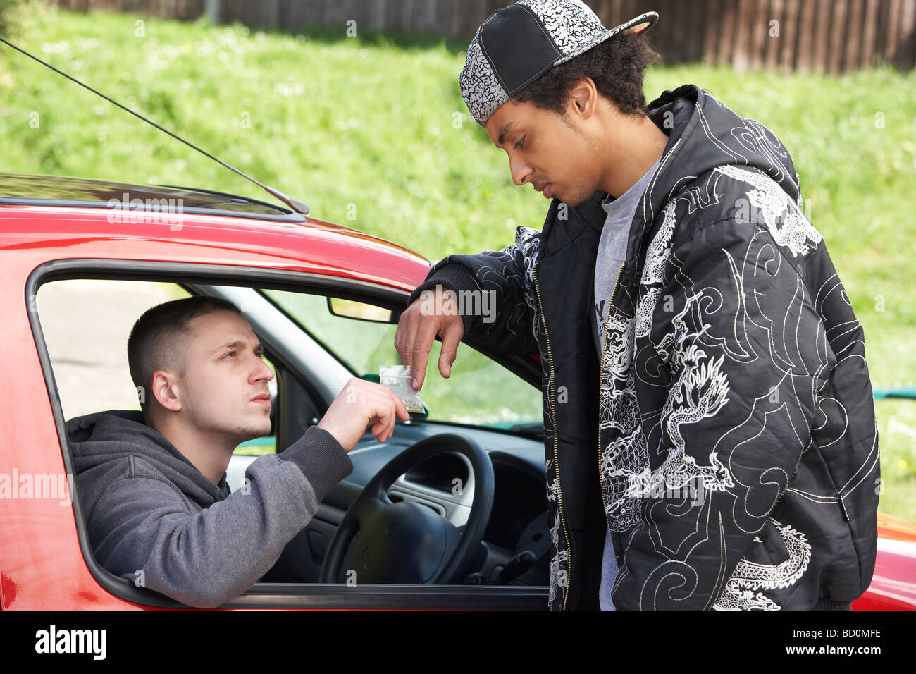 Young Man Dealing Drugs From Car - Stock Image