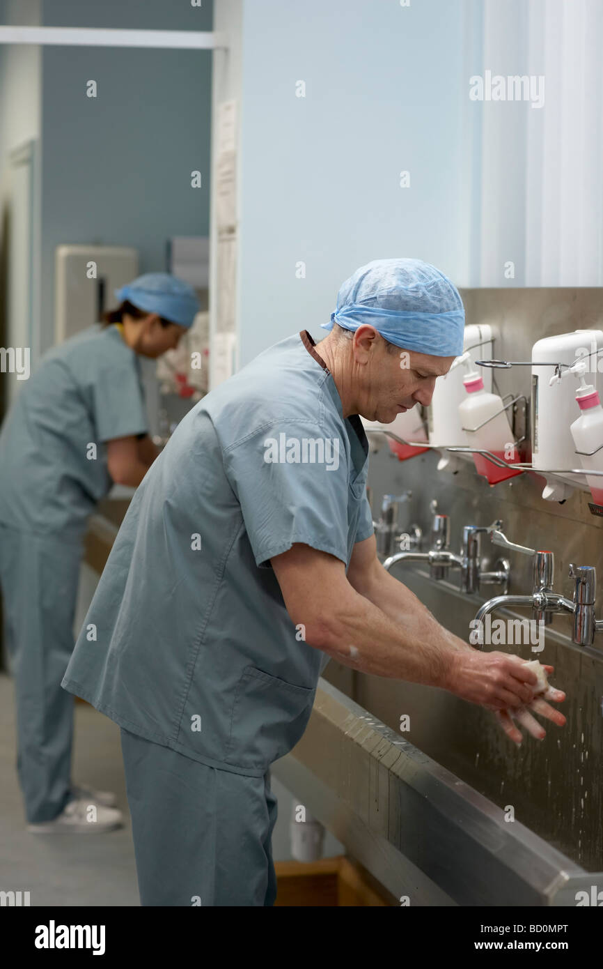 Medical staff in scrubs washing hands - Stock Image