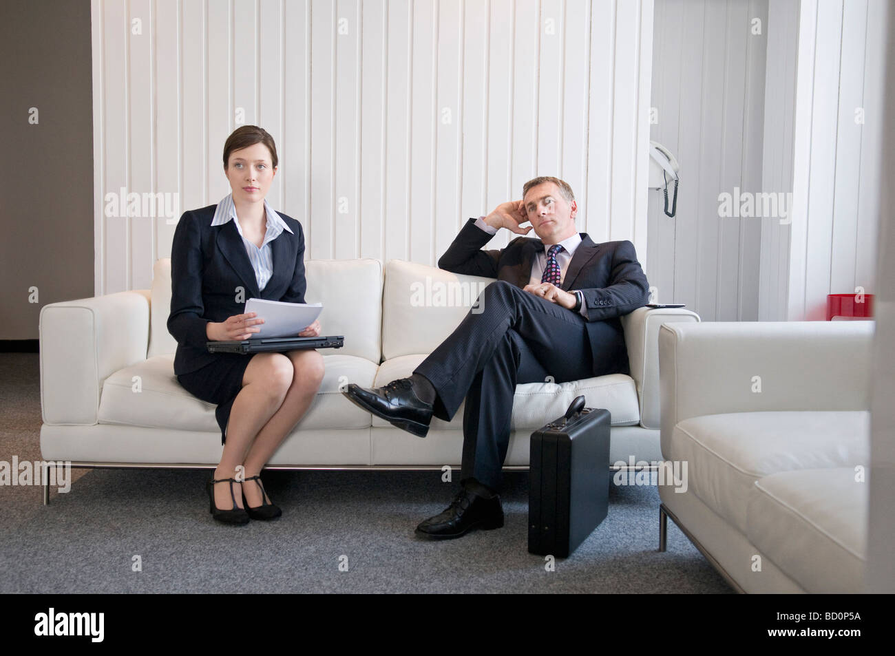 A business couple waiting in reception - Stock Image
