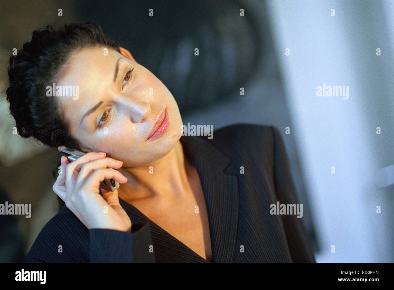 Young businesswoman using cell phone, looking away dreamily - Stock Image