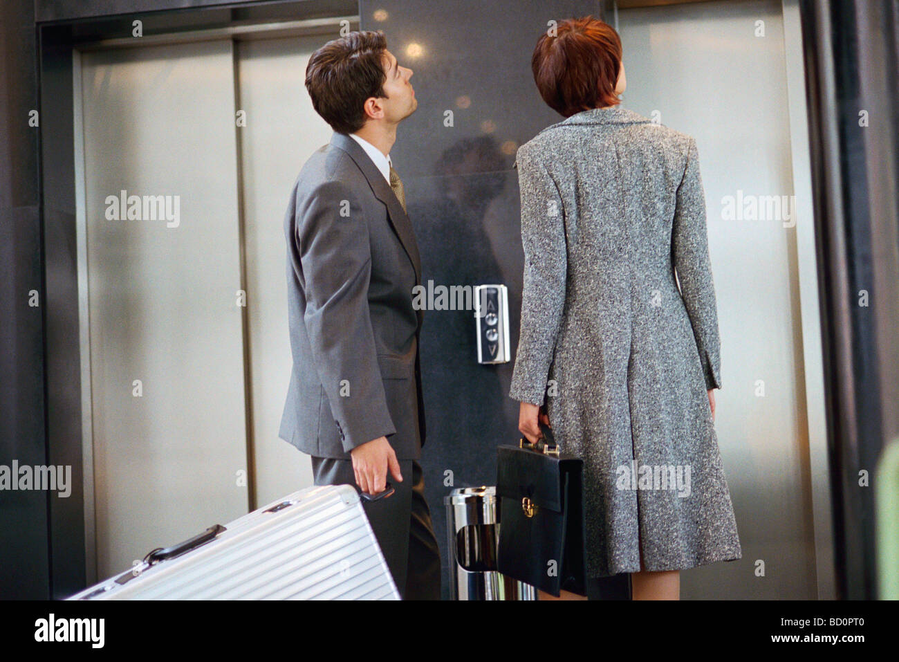 Business associates waiting for elevator - Stock Image