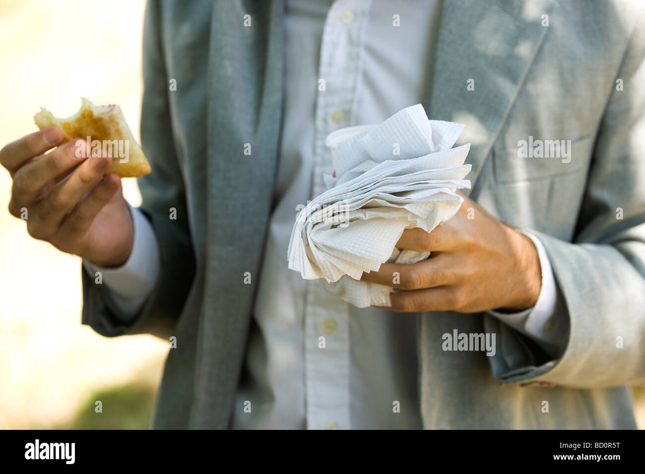 Person holding half eaten pastry in one hand and disposable cup and paper napkins in other hand - Stock Image