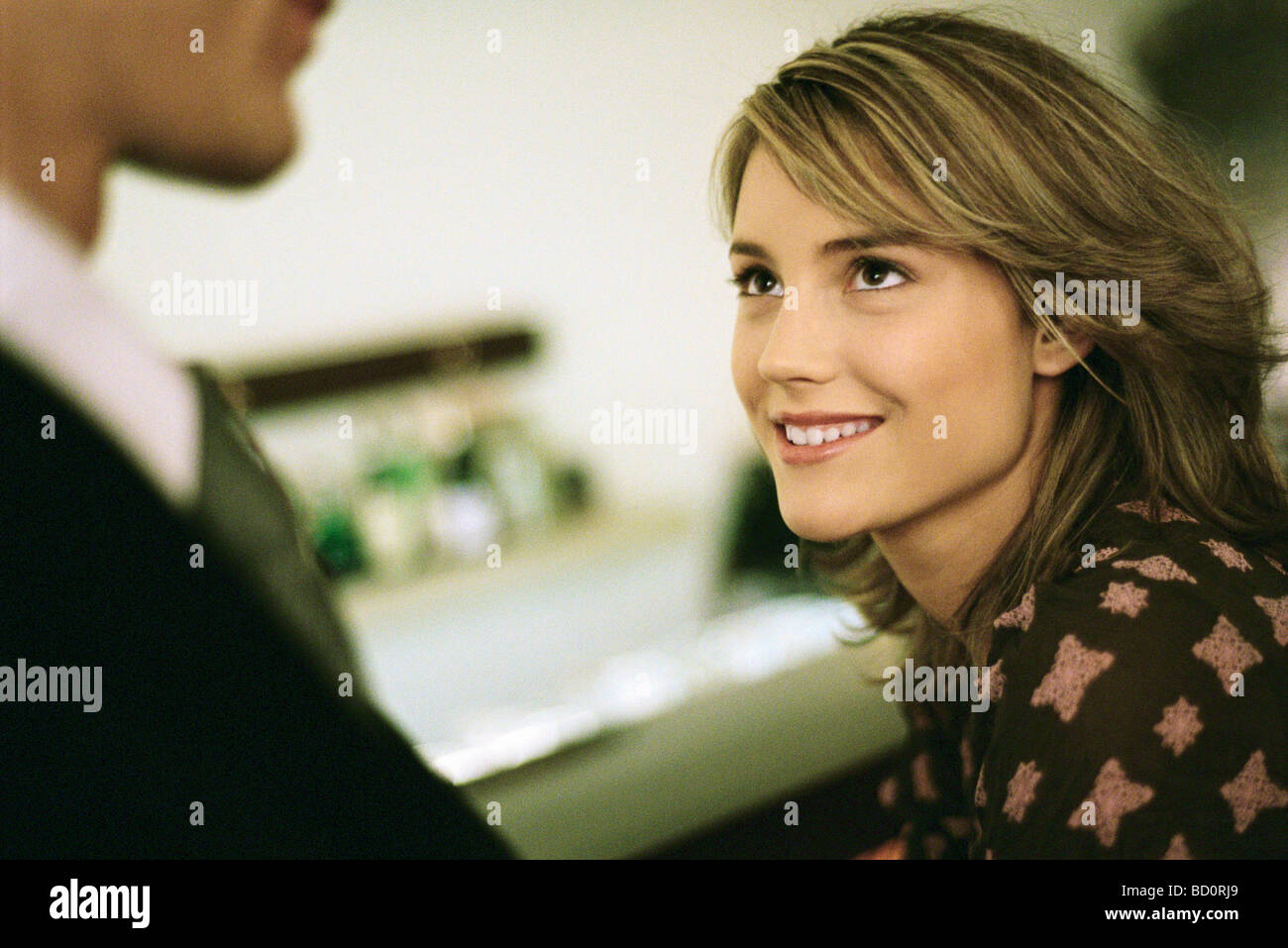 Young woman smiling looking up at man - Stock Image