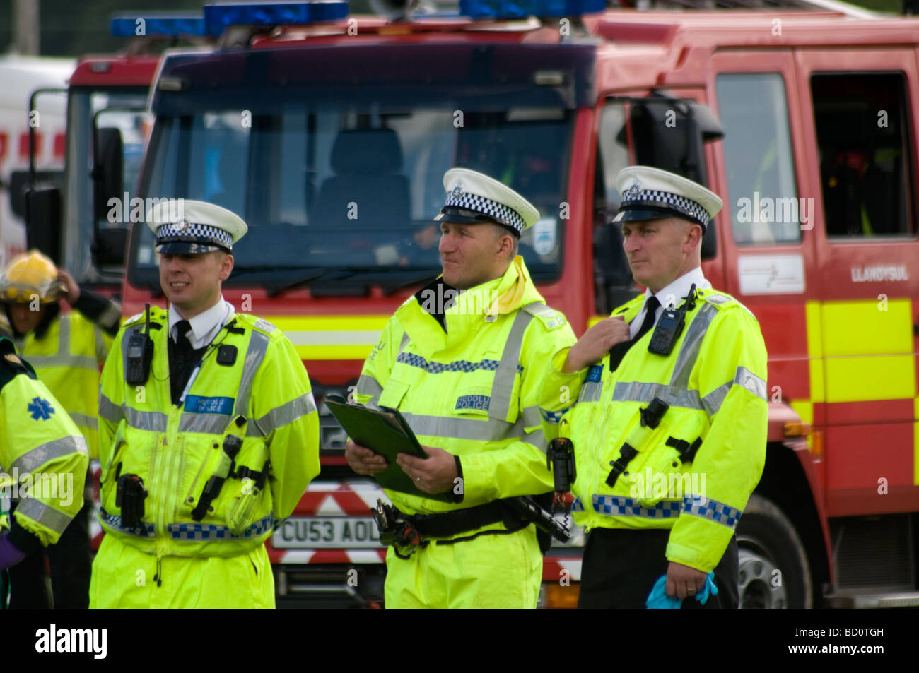 Three Traffic officers inspect a RTA while stood in front of a fire engine - Stock Image