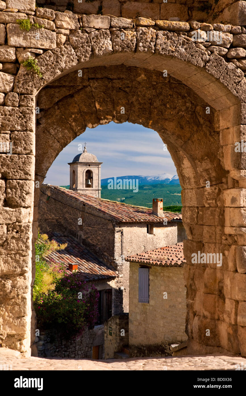Church bell-tower through Medieval stone gate with Mont Ventoux beyond, Lacoste Provence France - Stock Image