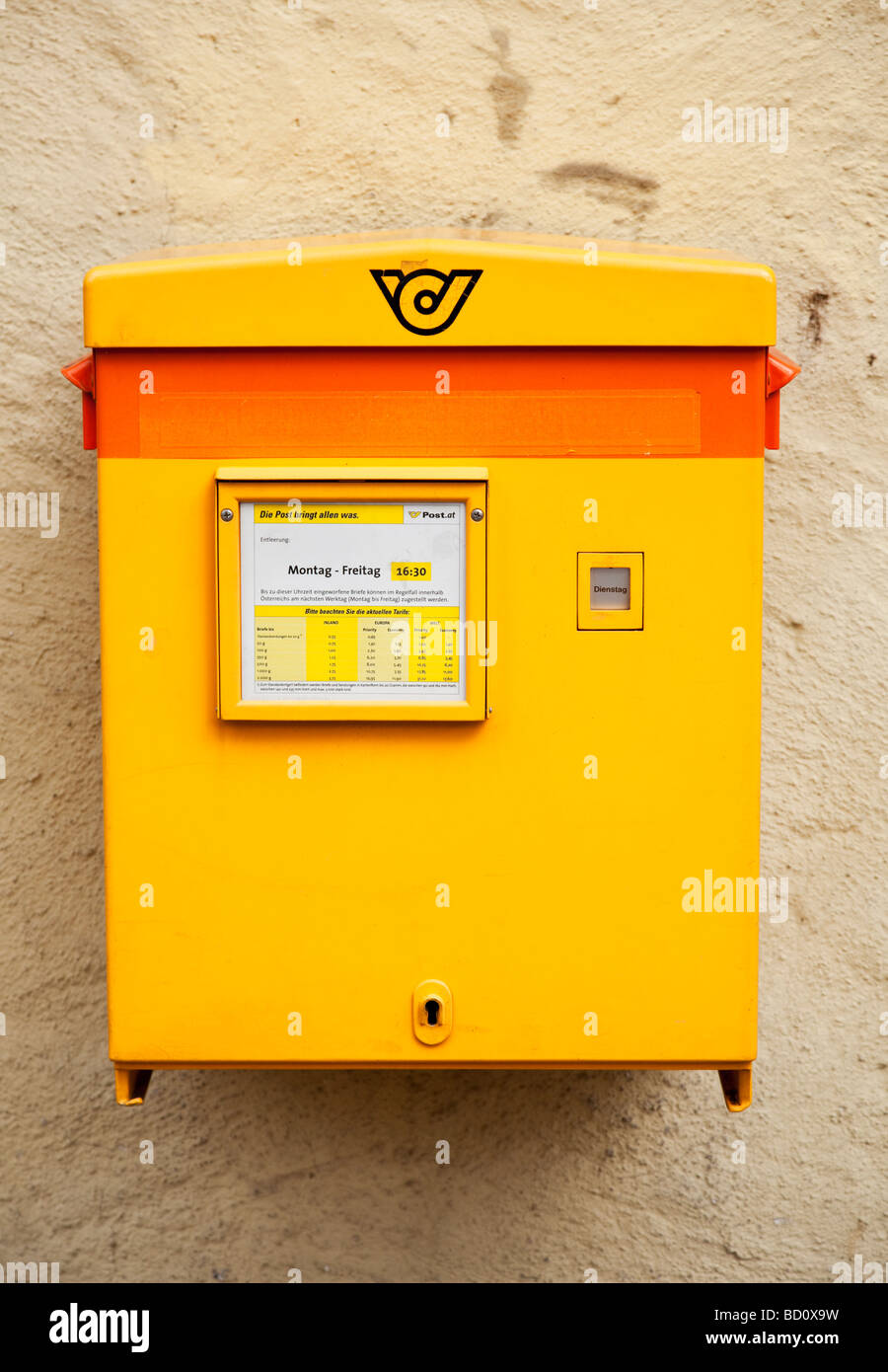 Postbox with collection times and prices in Austria, Europe - Stock Image