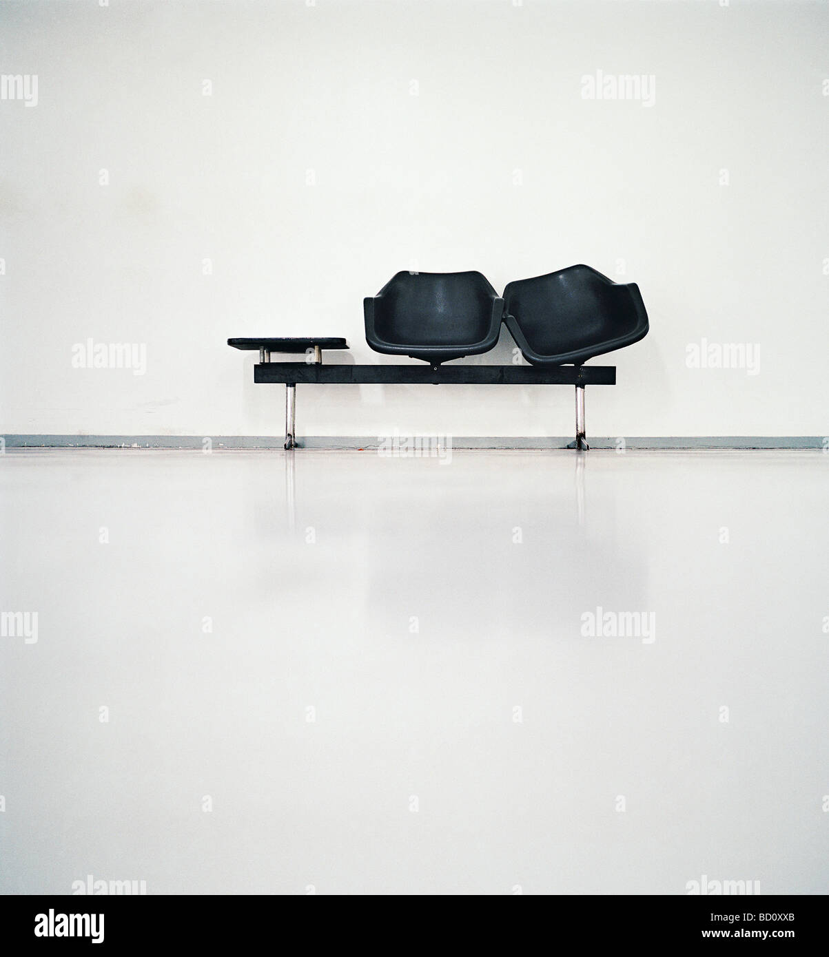 two black seats in an airport - Stock Image