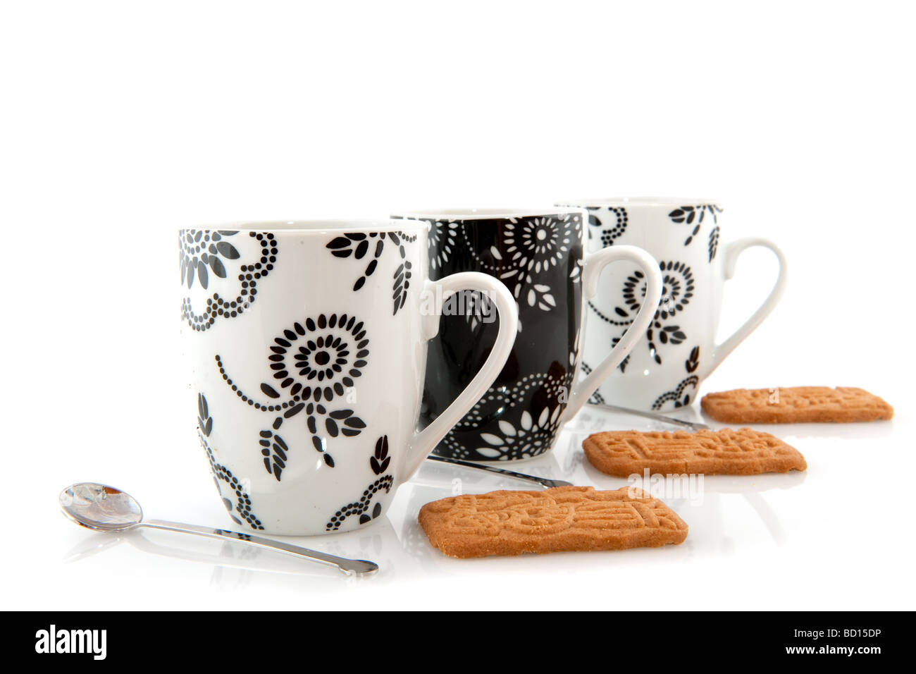 black and white coffee mugs with cookies and spoons - Stock Image