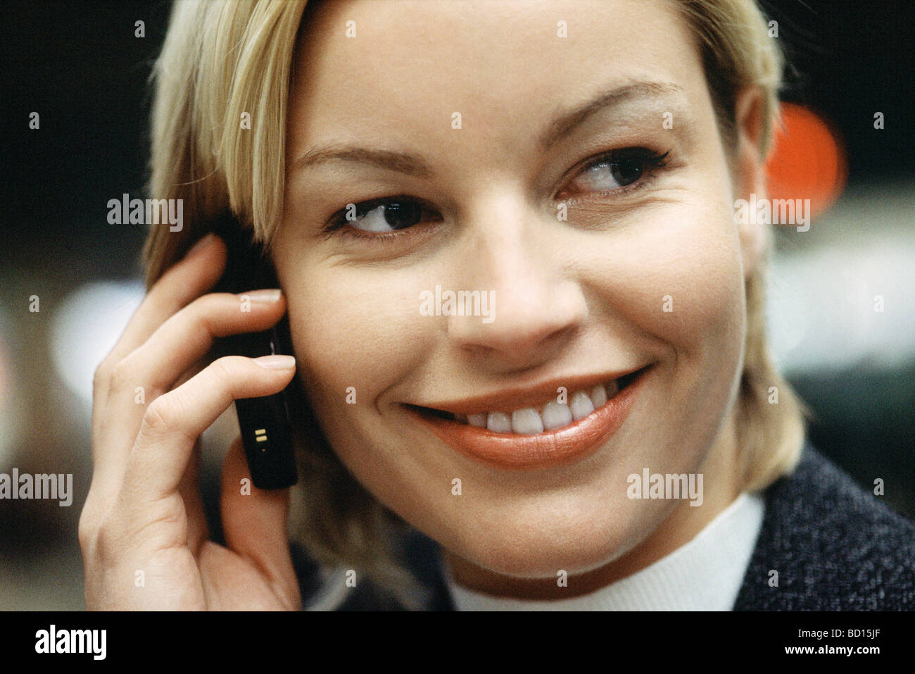 Woman phoning using cell phone smiling, glancing sideways, portrait - Stock Image