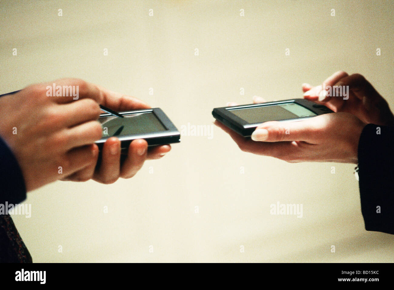 Two people exchanging information using personal digital assistants - Stock Image