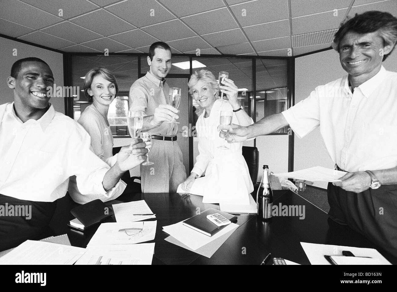 Business associates celebrating with champagne in office - Stock Image