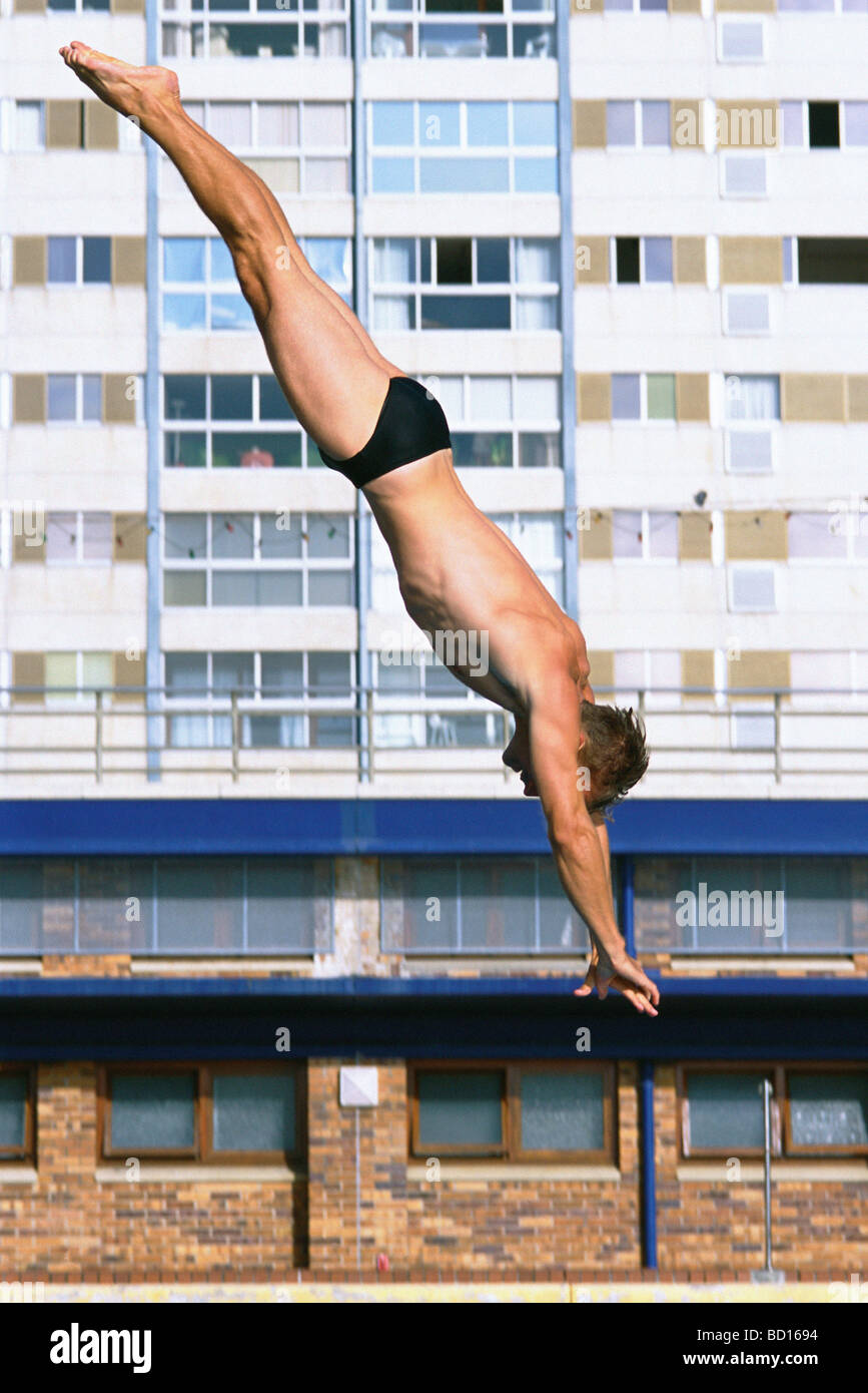 Man diving, high rise building in background Stock Photo