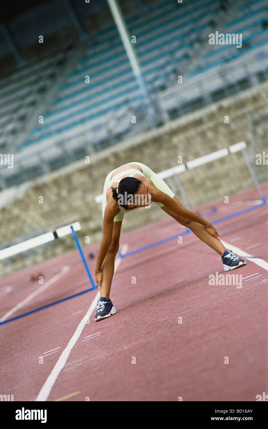 Woman doing stretches on running track - Stock Image