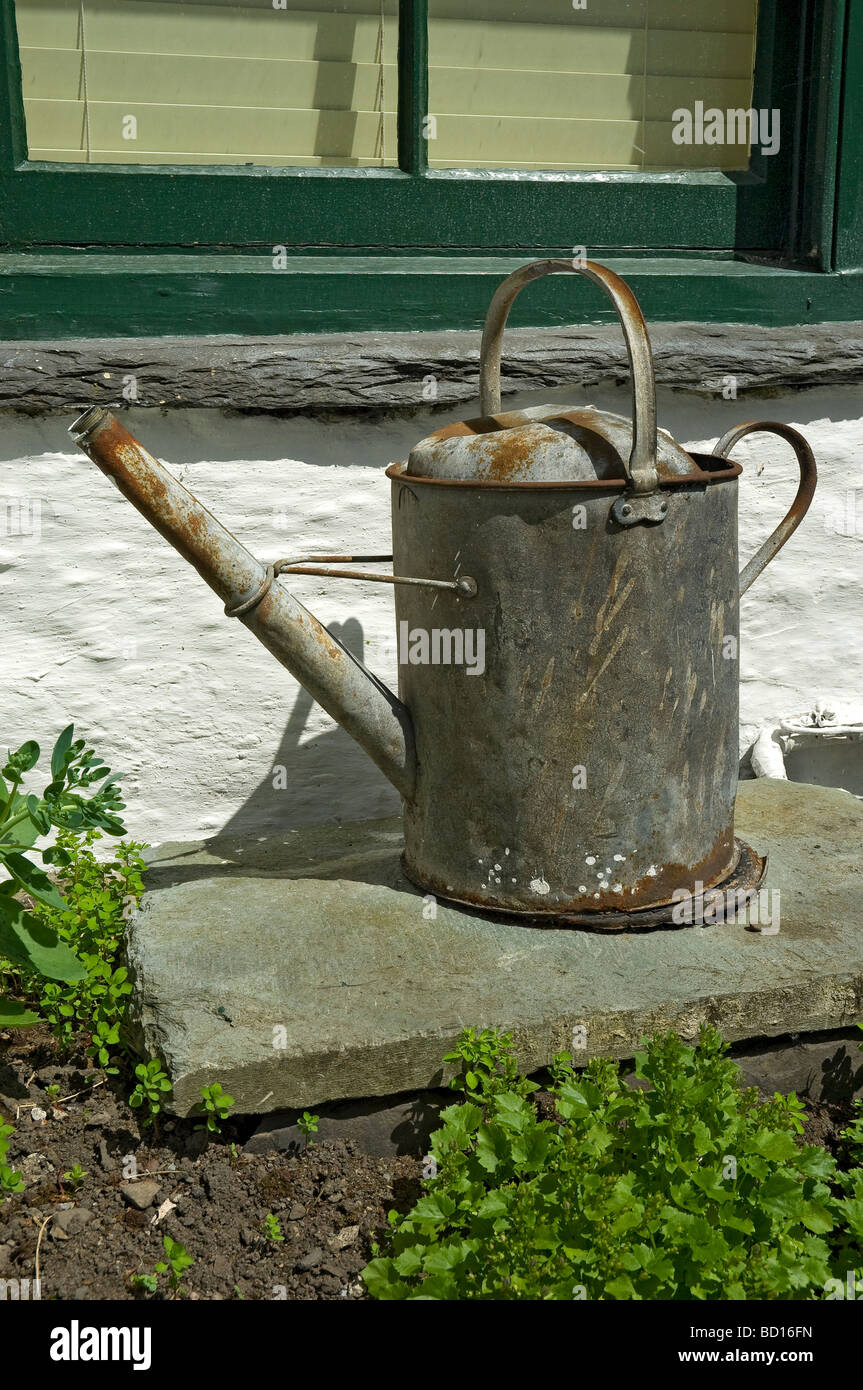 Old zinc watering can on piece of slate in garden England UK United Kingdom GB Great Britain Stock Photo