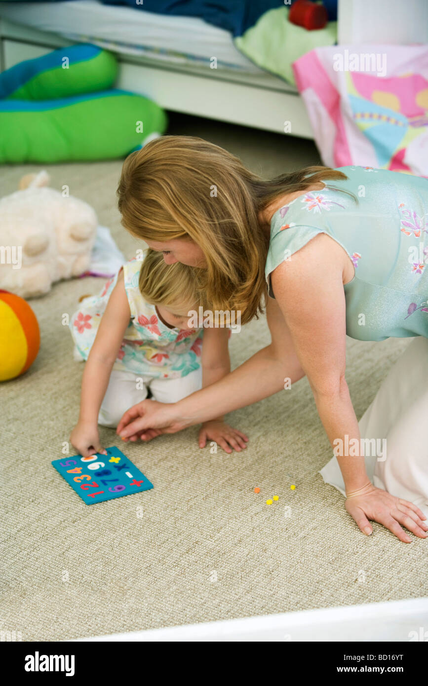 Mother and daughter playing together in child's bedroom Stock Photo