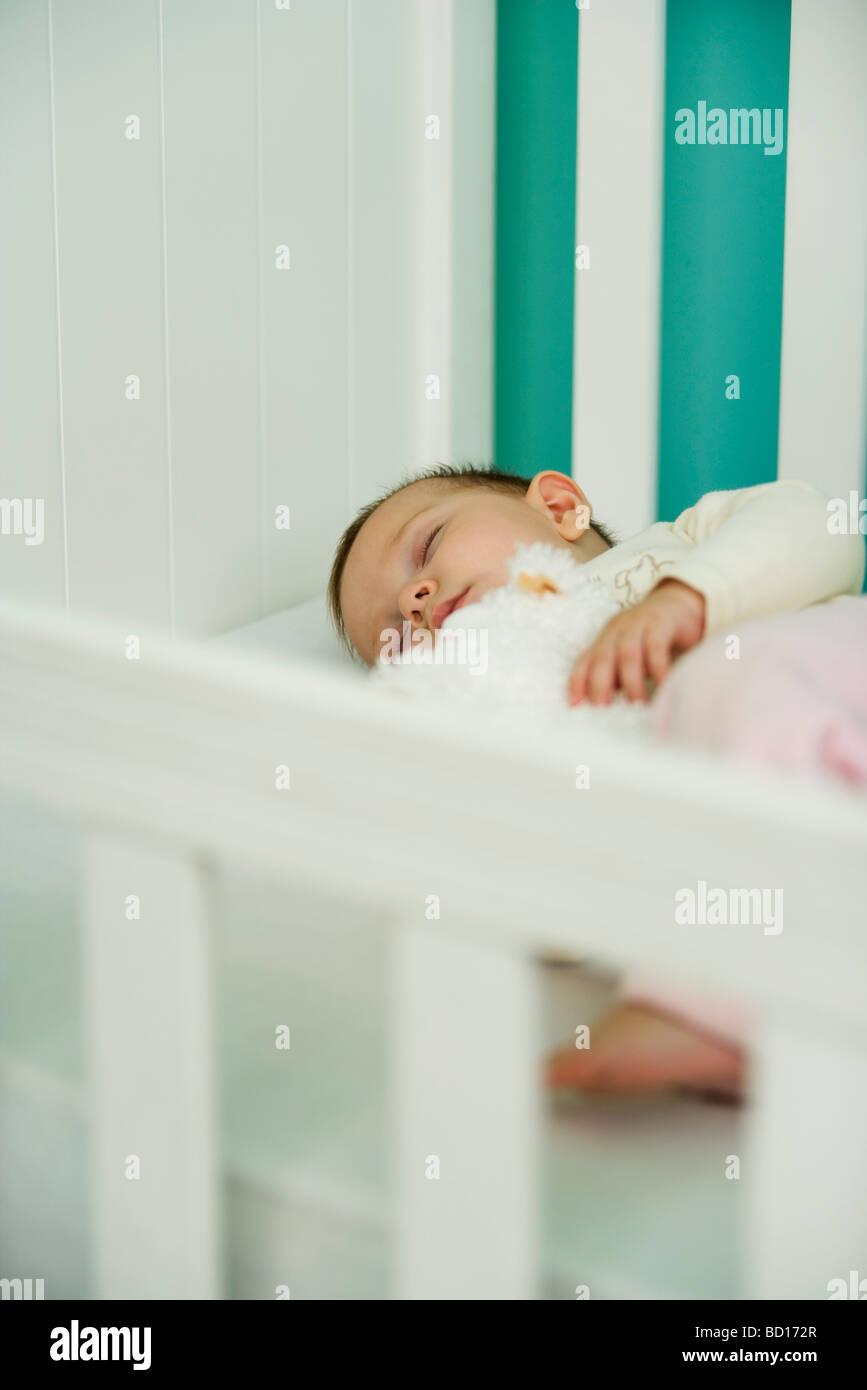 Baby sleeping in crib - Stock Image