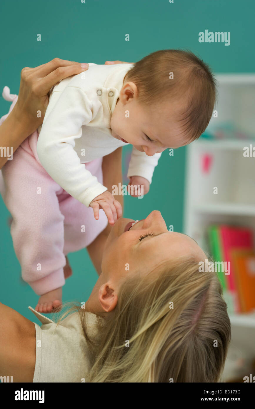 Young mother holding up baby, both smiling - Stock Image