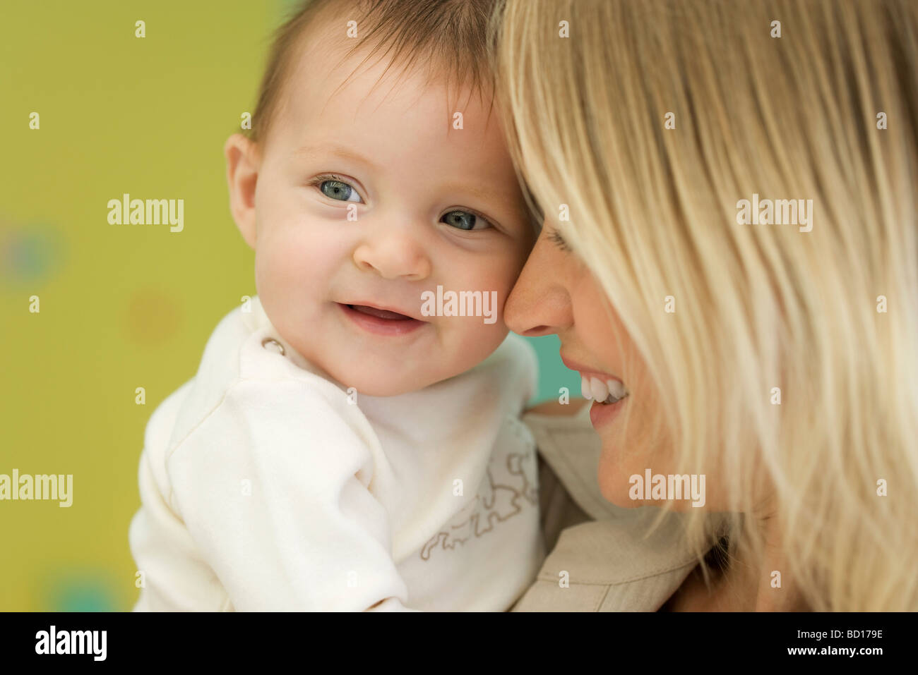 Mother holding baby next to face, close-up - Stock Image