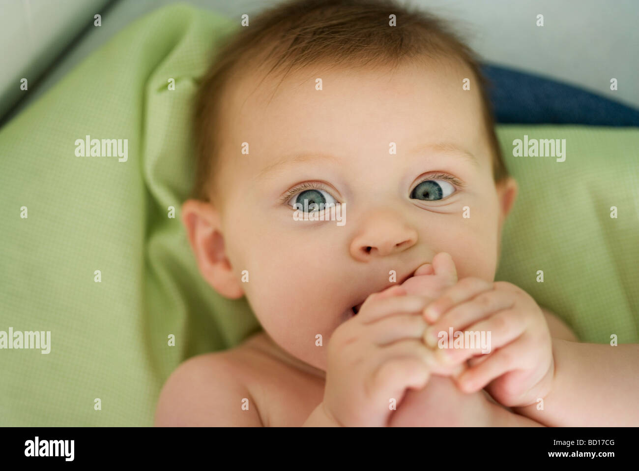 Baby with foot in mouth, close-up - Stock Image