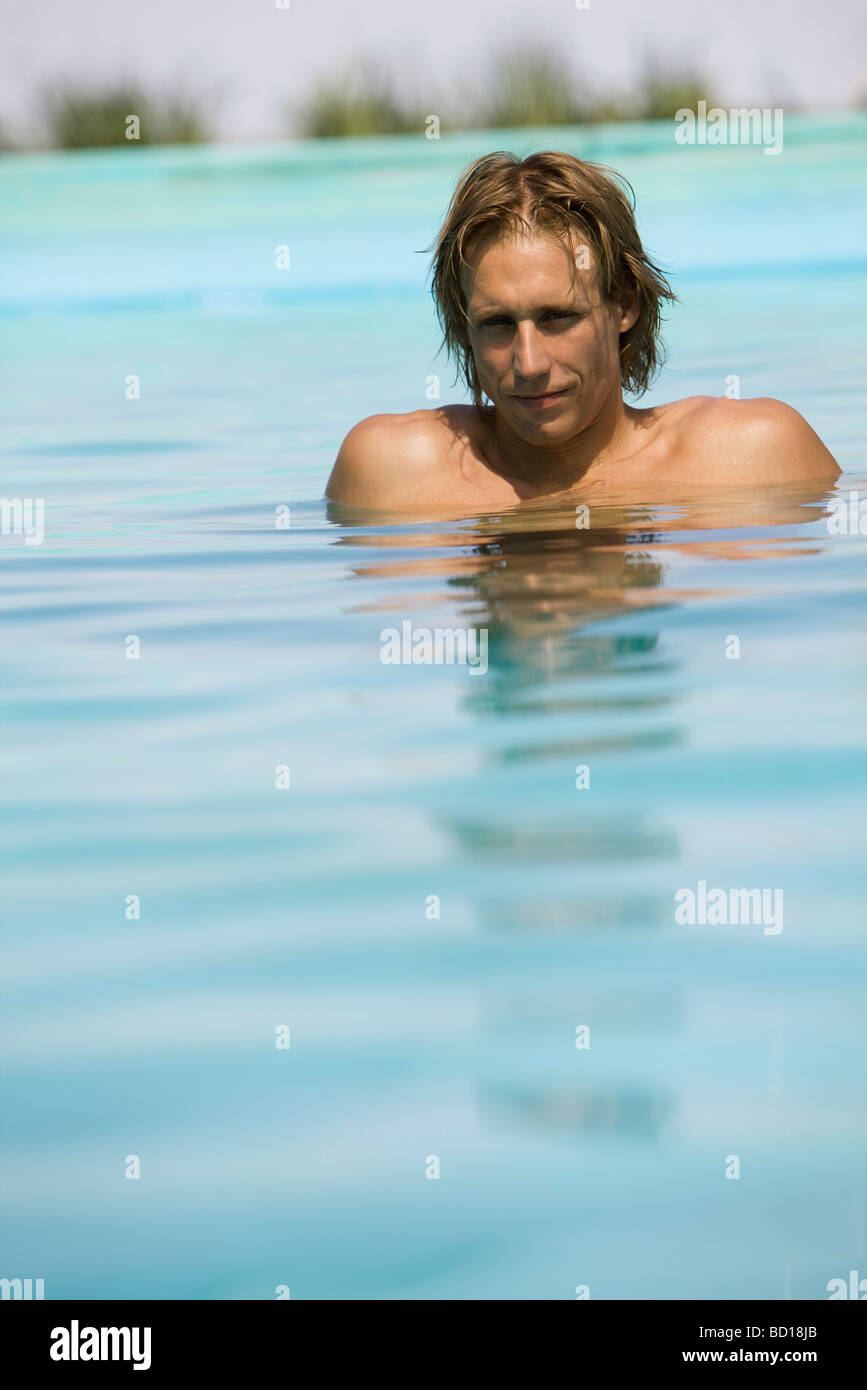 Man relaxing in shallow end of pool - Stock Image