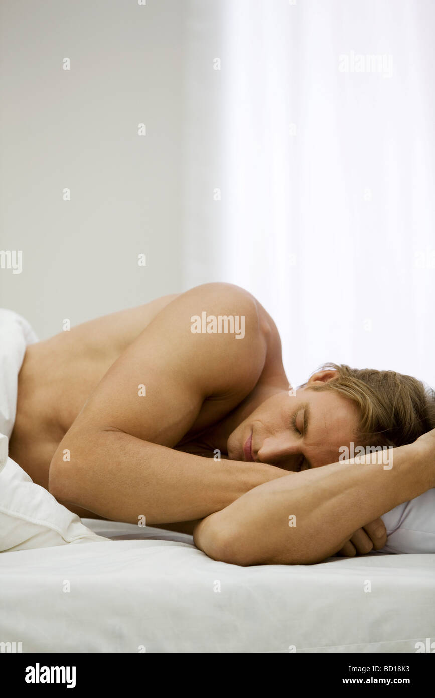 Man lying on side in bed sleeping - Stock Image
