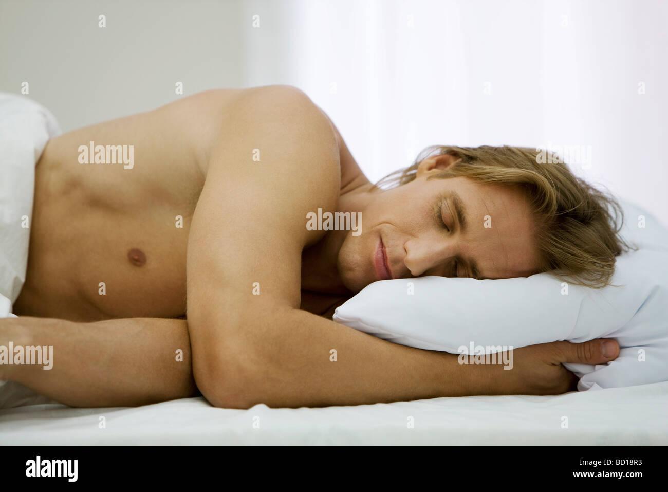 Man sleeping in bed - Stock Image
