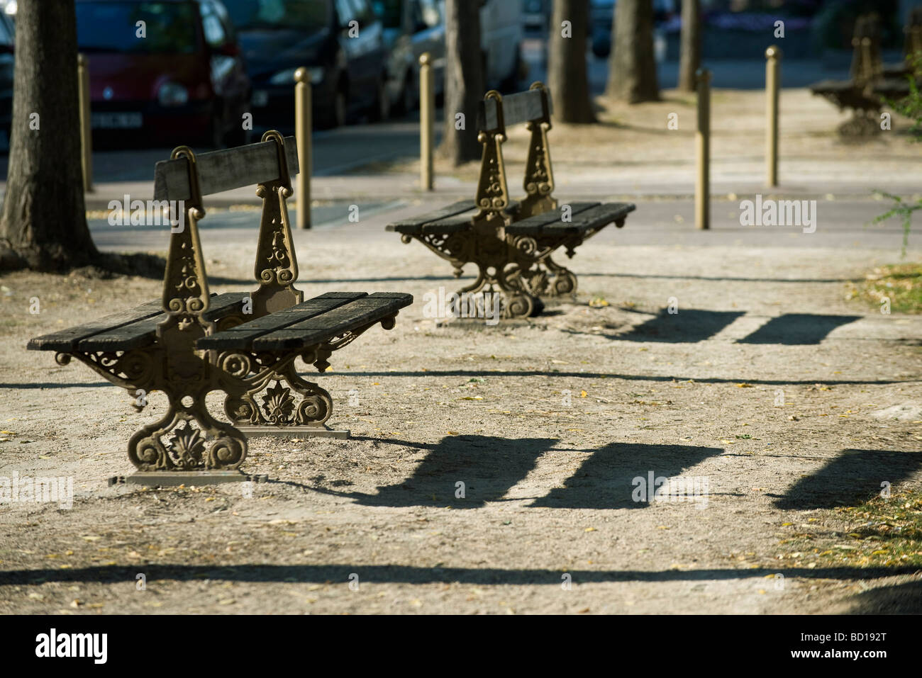 Ornate park benches casting shadows on ground Stock Photo