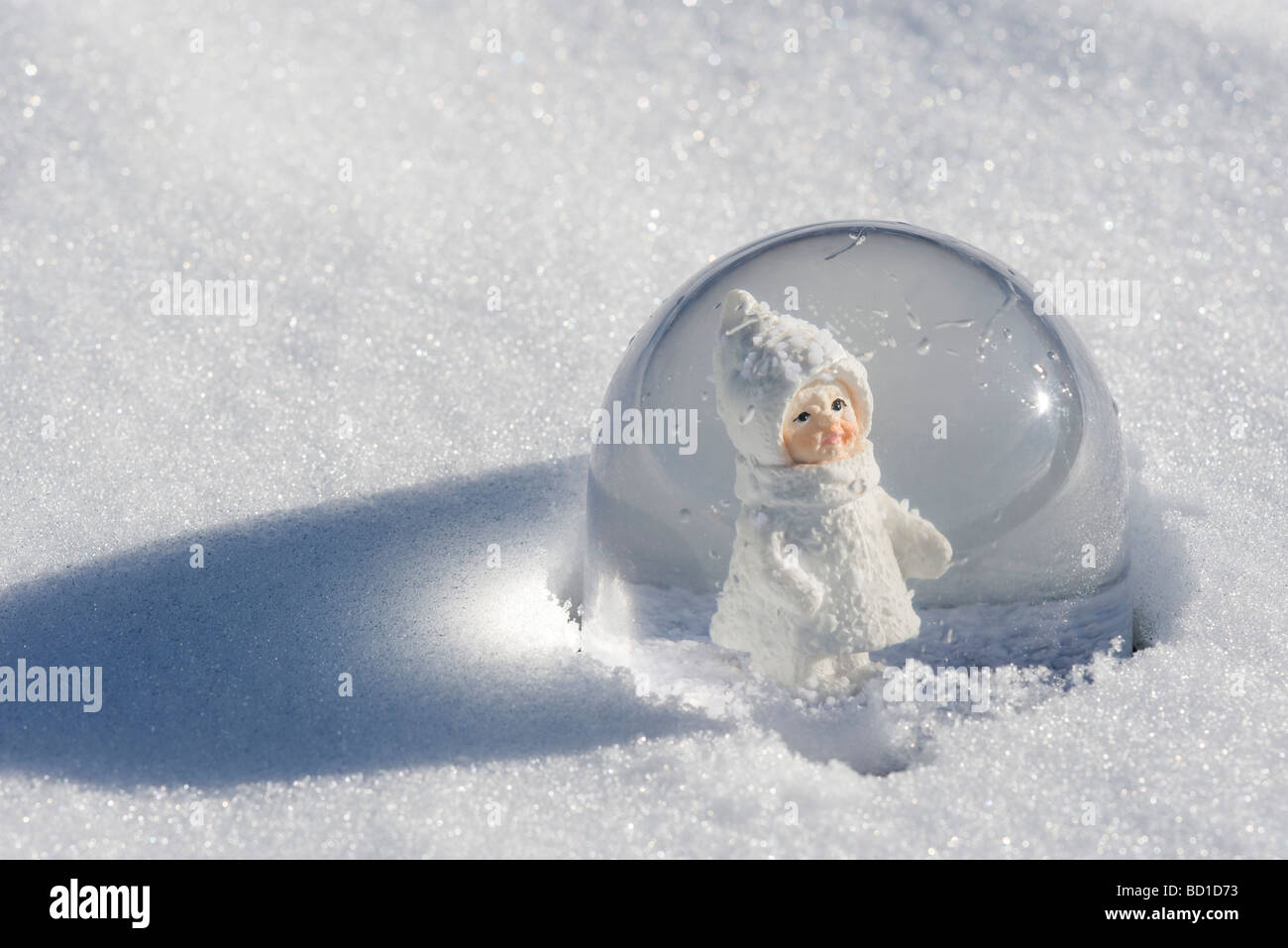 Snow globe in snow, figurine of little girl wearing winter coat and hat looking out Stock Photo