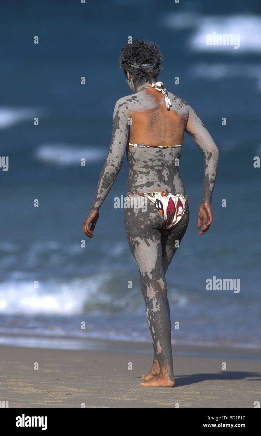 Girl walking along beach covered with mud from therapeutic  mud bath - Stock Image