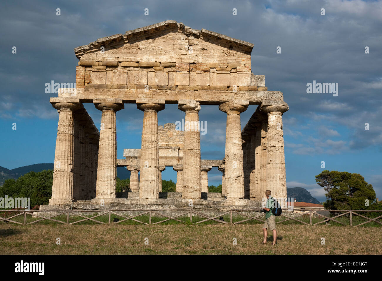 A man admires the Temple of Ceres at Paestum, Italy, viewed from the west. - Stock Image