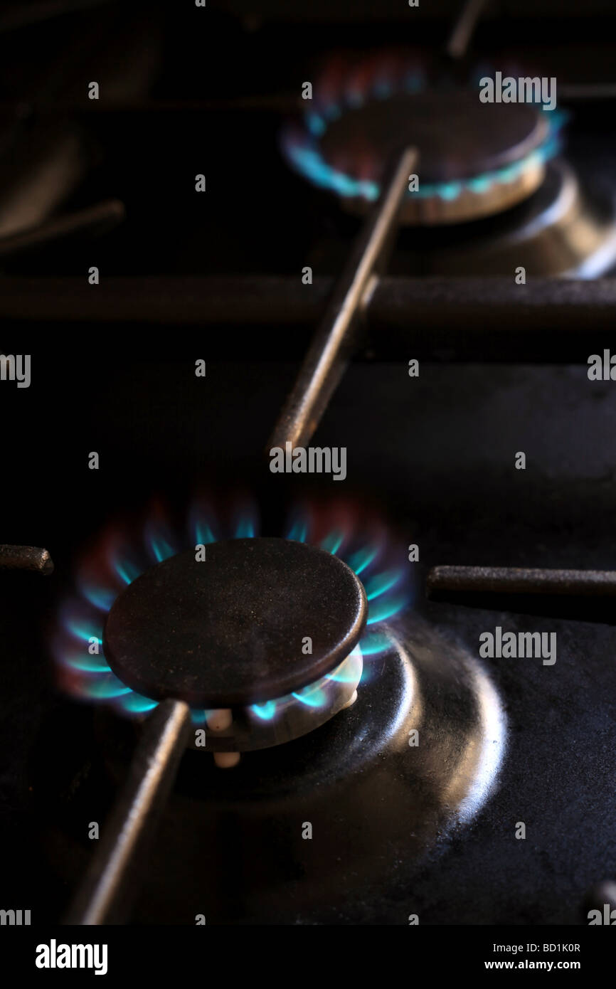 Lit gas burners on a domestic cooker - Stock Image