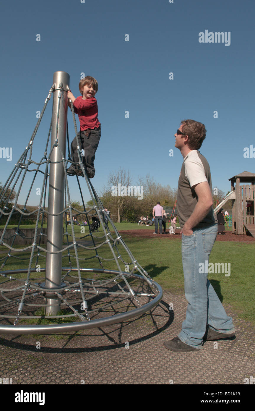three year old boy in playground on rotating climbing frame watched over by his father Stock Photo