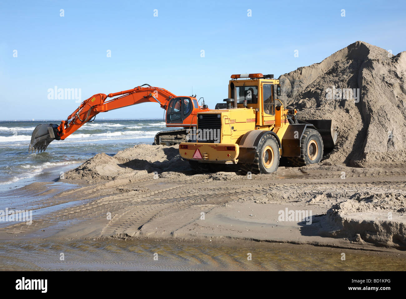 Navvy and front loader digging and moving sand in a coast protection project. - Stock Image