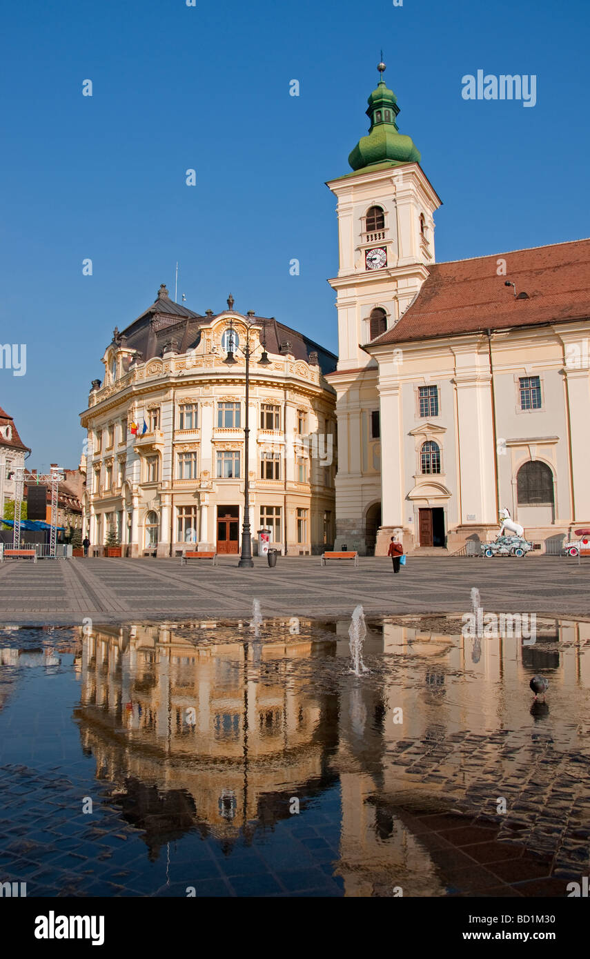 Romania's Sibiu City Hall and Holy Trinity Roman Catholic Cathedral tower on the Piata Mare Square pedestrian plaza Stock Photo