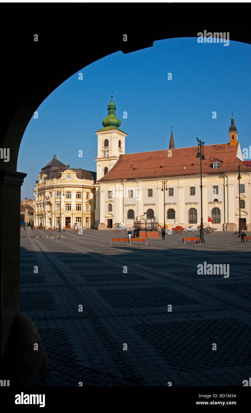 Romania's Sibiu City Hall and Holy Trinity Roman Catholic Cathedral tower on the Piata Mare Square pedestrian - Stock Image