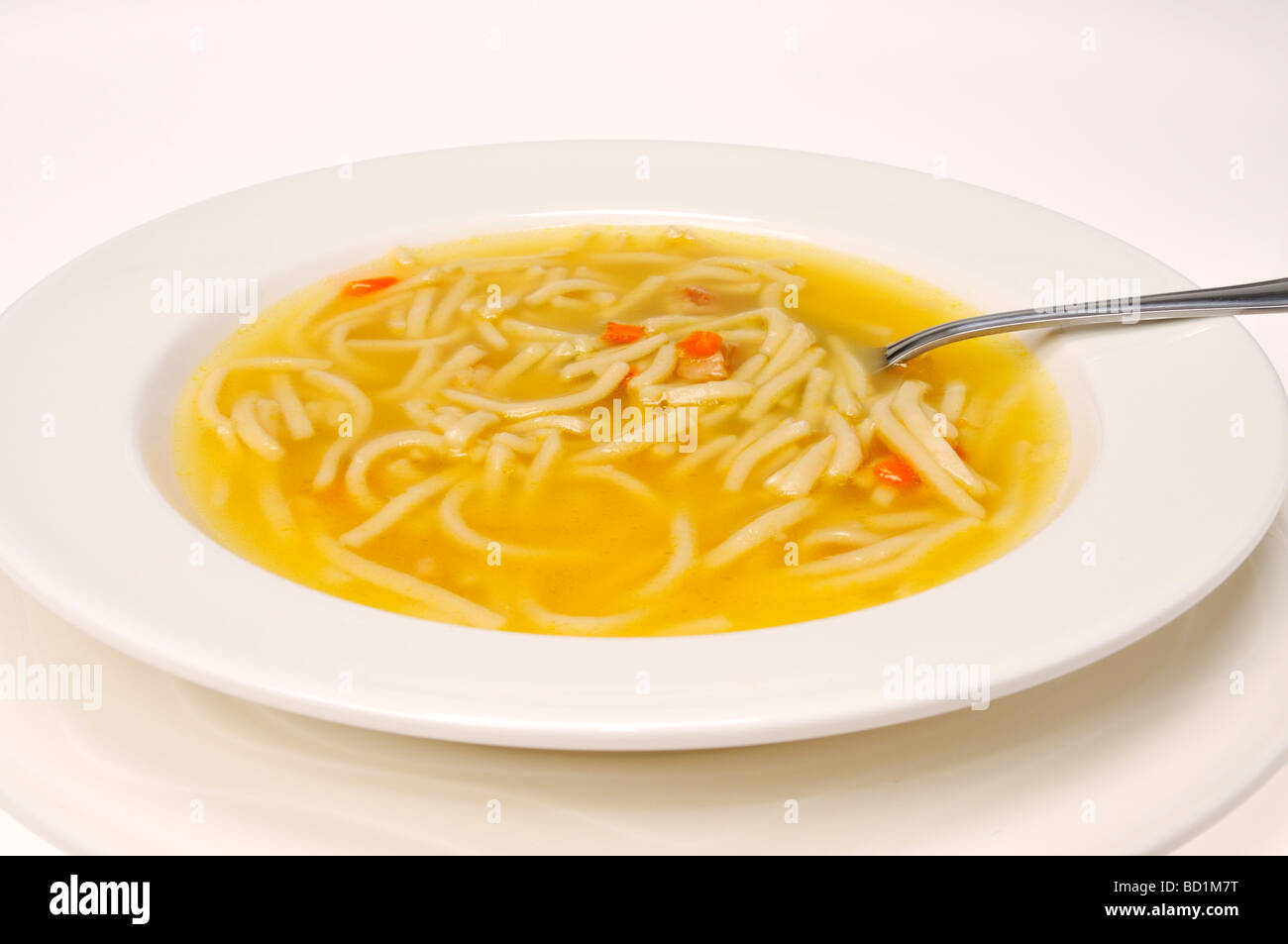 Bowl of chicken noodle soup with spoon on white background. - Stock Image