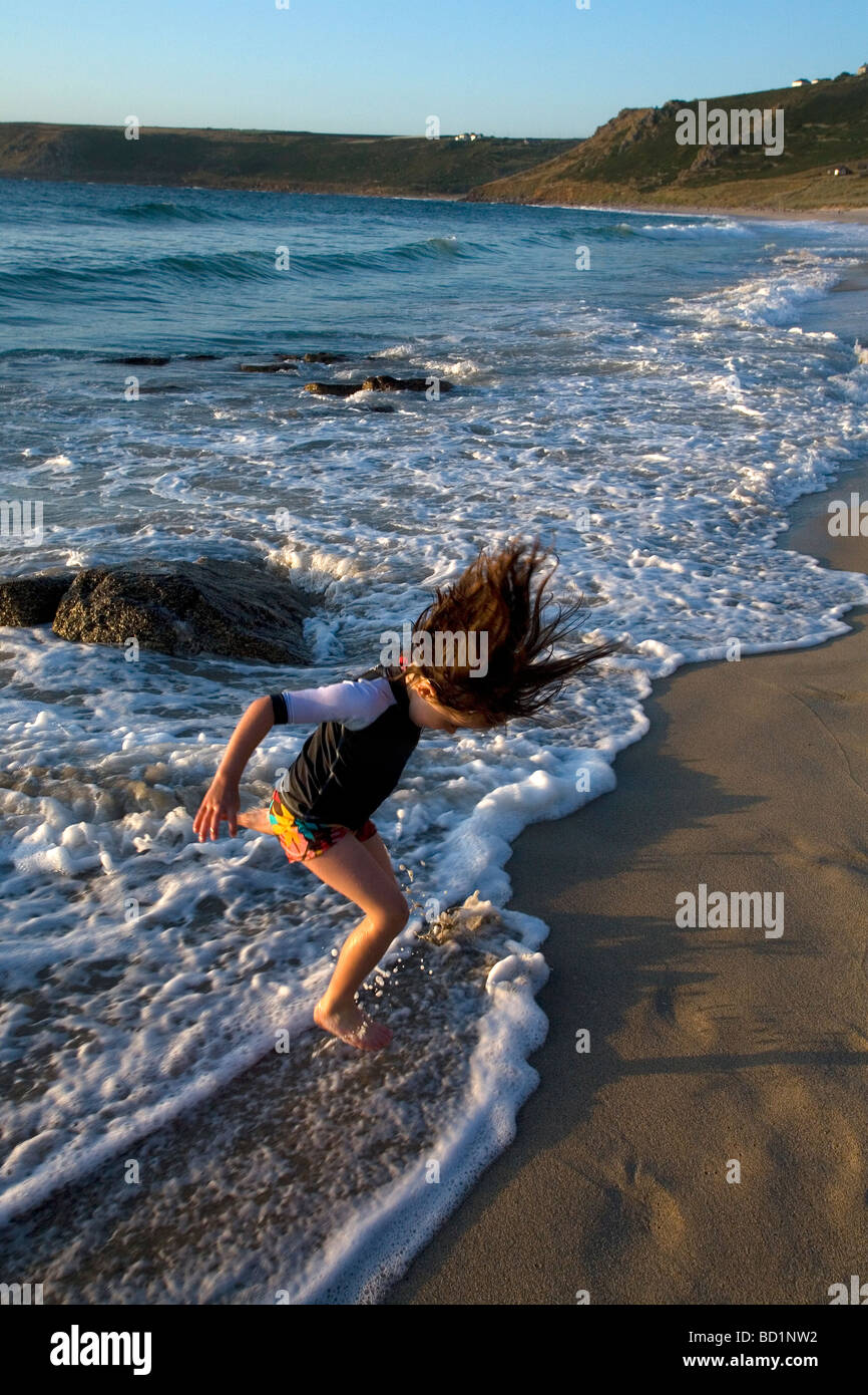Young girl enjoying playing at jumping over gentle waves rolling on the beach. Good fun and memories of childhood - Stock Image