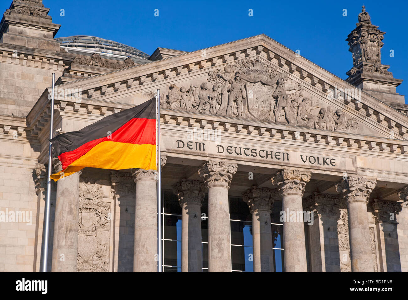 Europe Germany Berlin Reichstag German Parliament building German flag in foreground - Stock Image