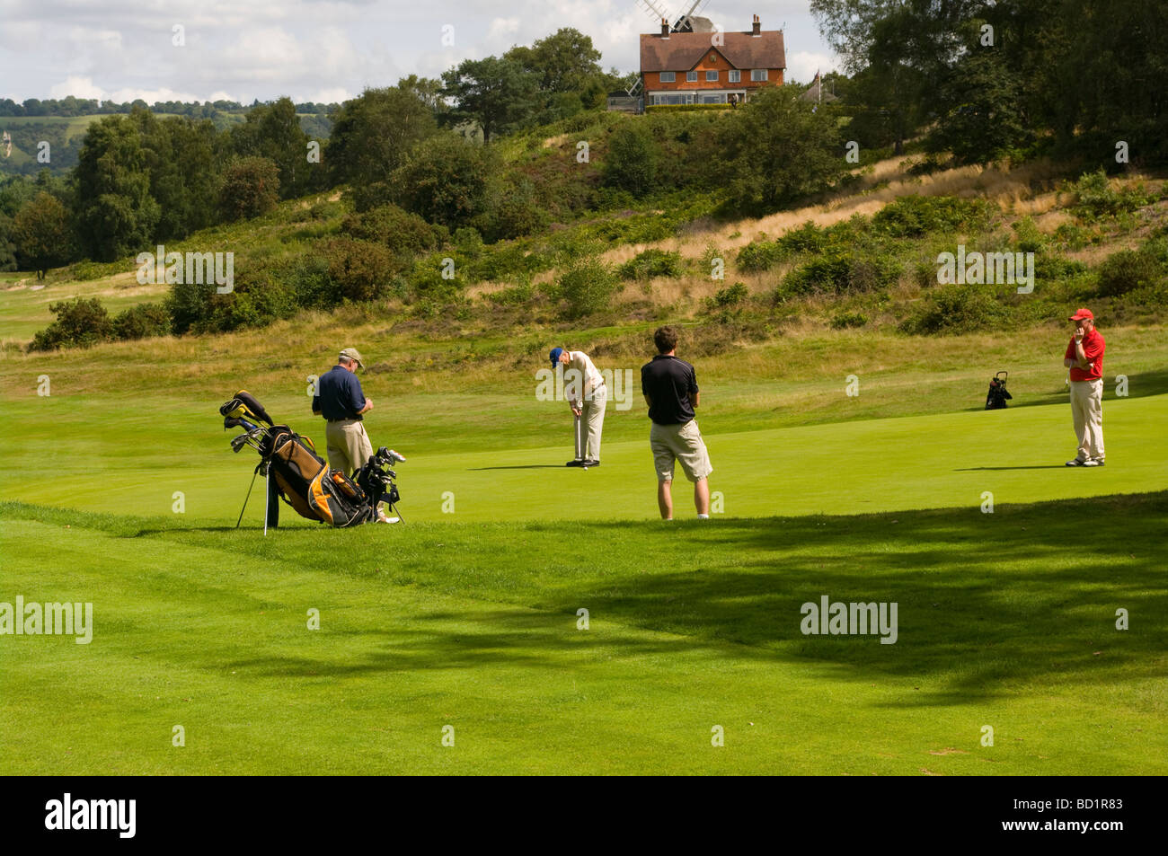 Golfers On Reigate Heath Golf Course With The Clubhouse In The Background Surrey England - Stock Image