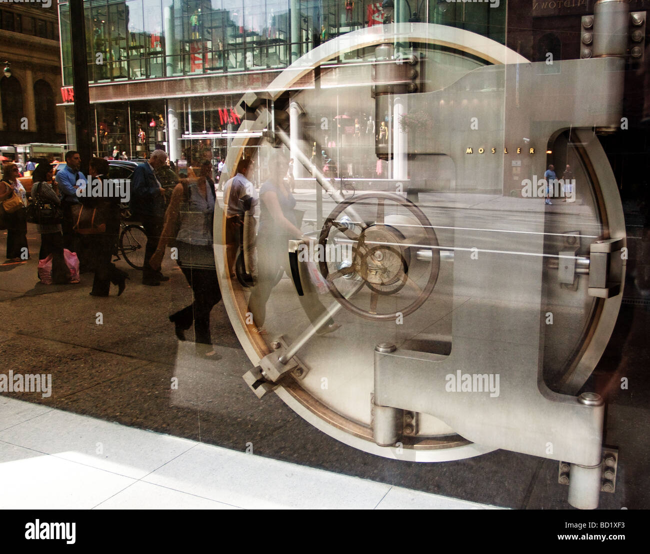 Silver bank vault door with reflection street in glass exhibition. - Stock Image
