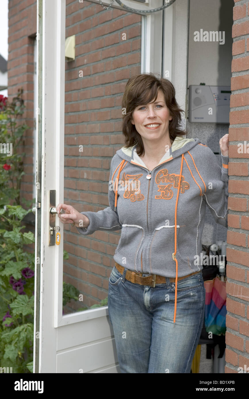 Happy adult woman standing in open door, could be mother waiting for her child to arrive home safe. - Stock Image