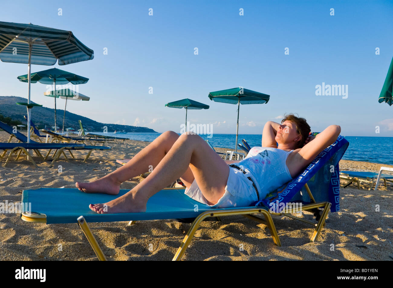 Woman relaxing on sunbed in late afternoon sunshine on beach at Skala on the Greek island of Kefalonia Greece GR Stock Photo