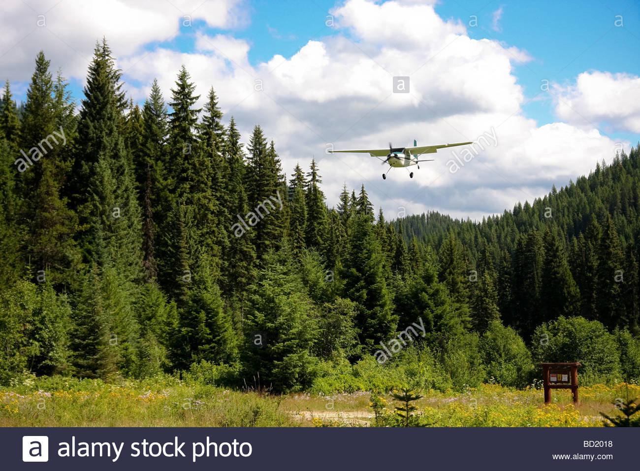 A single engine small private aircraft prepares to land at the remote Cayuse emergency landing strip in the wilderness - Stock Image