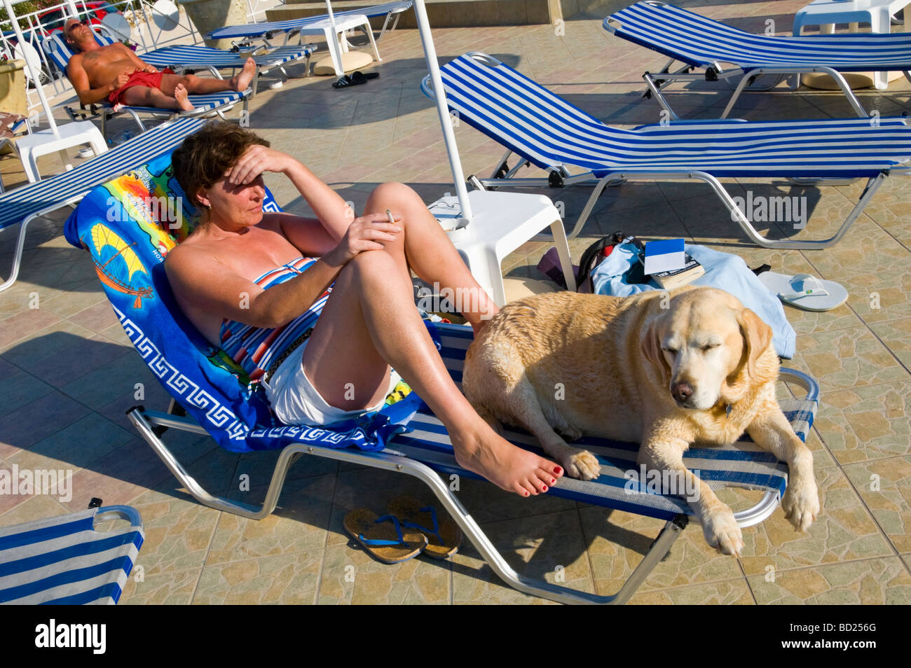 Woman lying on poolside sunbed with golden labrador at hotel near Skala on the Greek Mediterranean island of Kefalonia - Stock Image