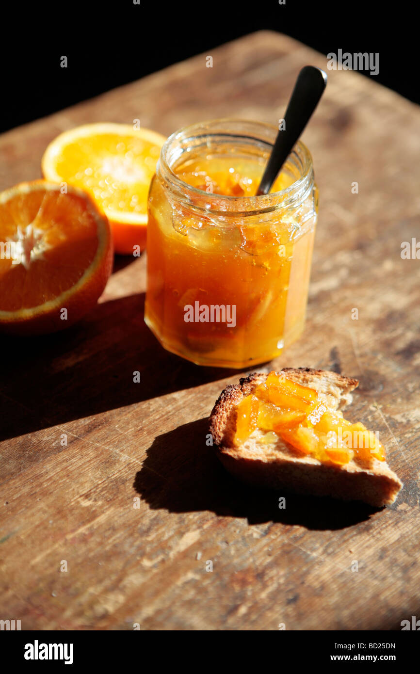 Jar of marmalade, oranges and marmalade on toast. - Stock Image