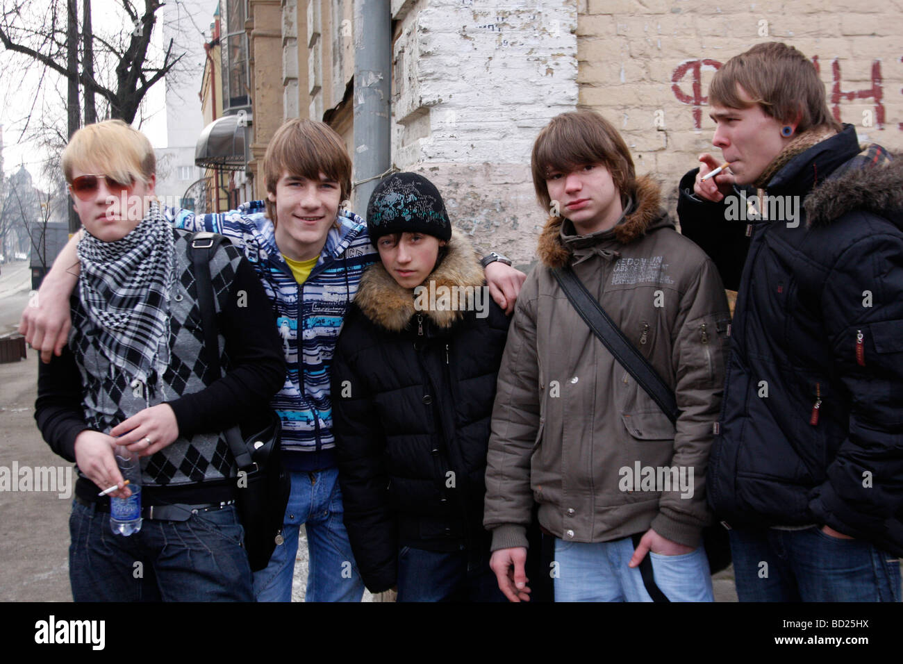 Ukrainian teenagers, students of hair stylists school chill out on the street in Kyiv (Kiev) Ukraine. Only one smiles - Stock Image